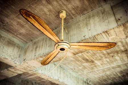Raw concrete and a rusted fan