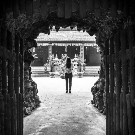Peering through the sculpted gateway to a temple across from Han